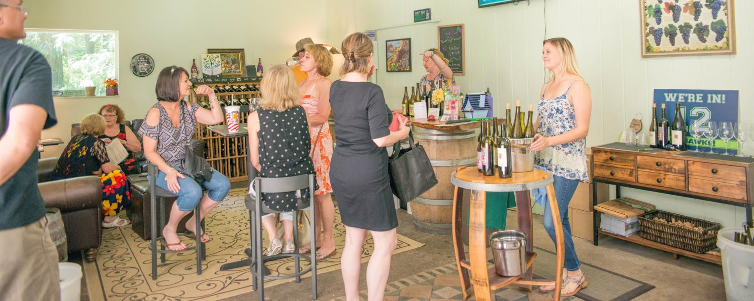 Inside Cedar River Cellars Tasting Room with people enjoying wine and conversation.